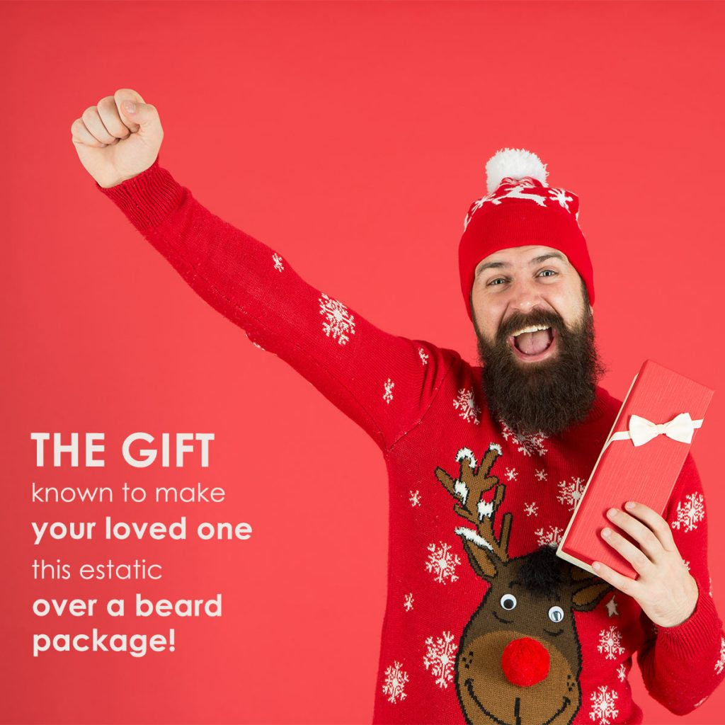 Happy beard man with a christmas gift in his hand. Gift is the Beard Baus grooming kit