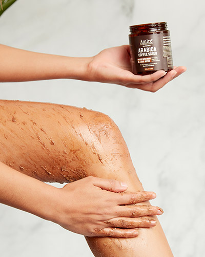 Model holding Amire Cosmetics Arabica Coffee Scrub in her left hand and applying the scrub with her right hand on her leg.