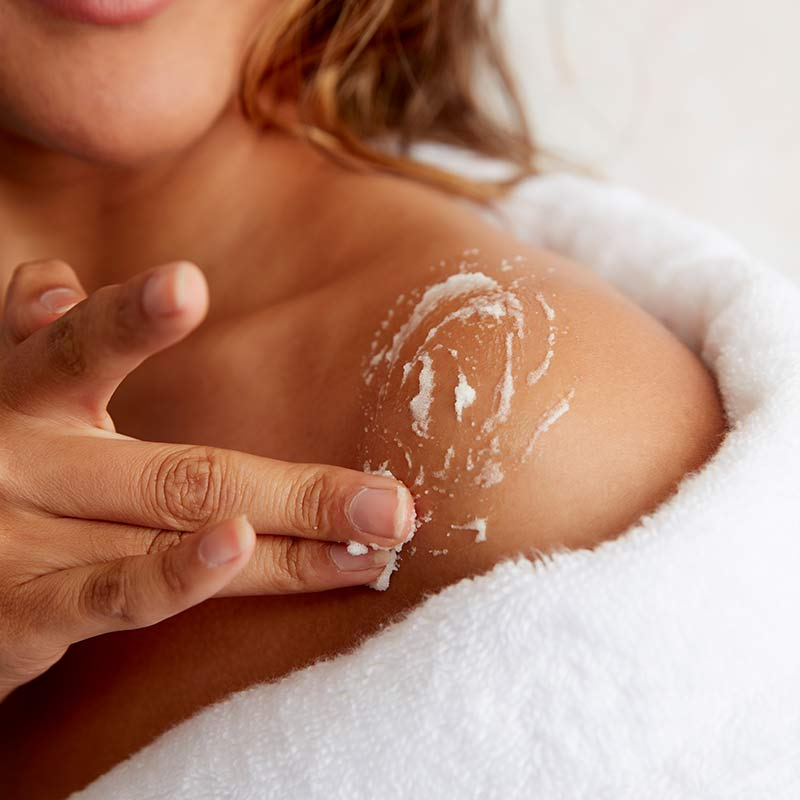 Girl wearing a robe applying a body scrub to her shoulder to exfoliate.