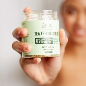 Model holding Amire Cosmetics Tea Tree Oil Body scrub.