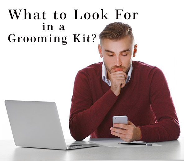 What to look for in a beard grooming kit? Man researching for beard grooming kits.Man with his laptop open while looking at his phone. Looking for different grooming kits and what is included in a good kit.