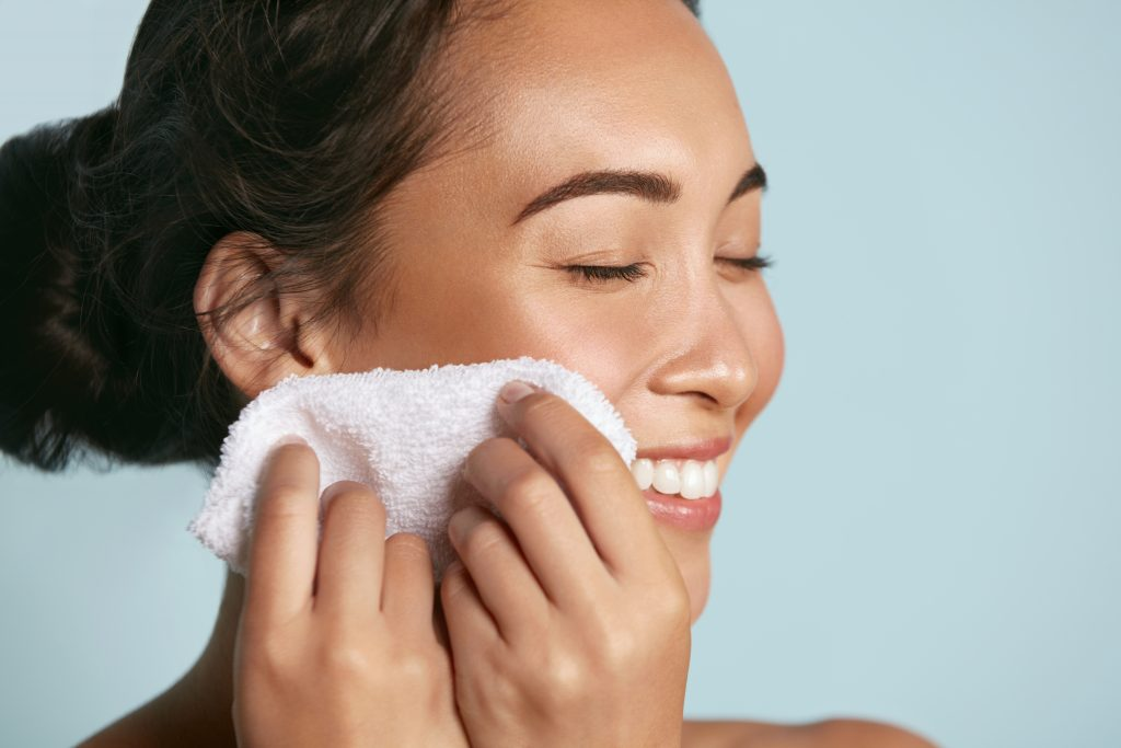 woman washing face with a wash cloth