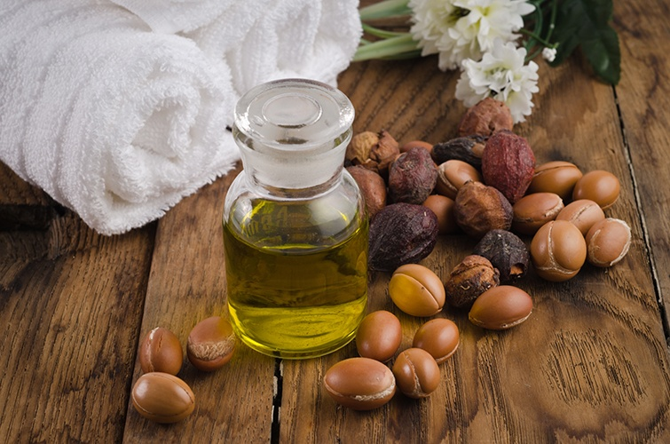 argan oil in glass jar with argan seeds and flower next to towel