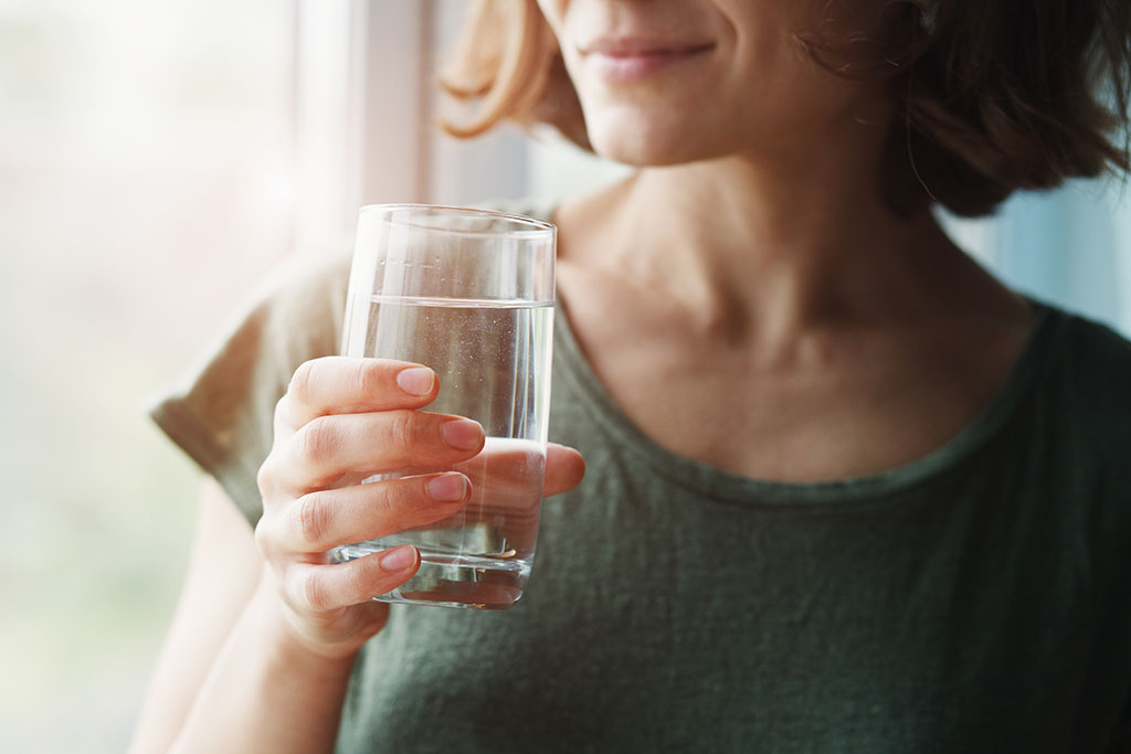 brunette woman in olive green scoop neck shirt smiling and holding glass of drinking water