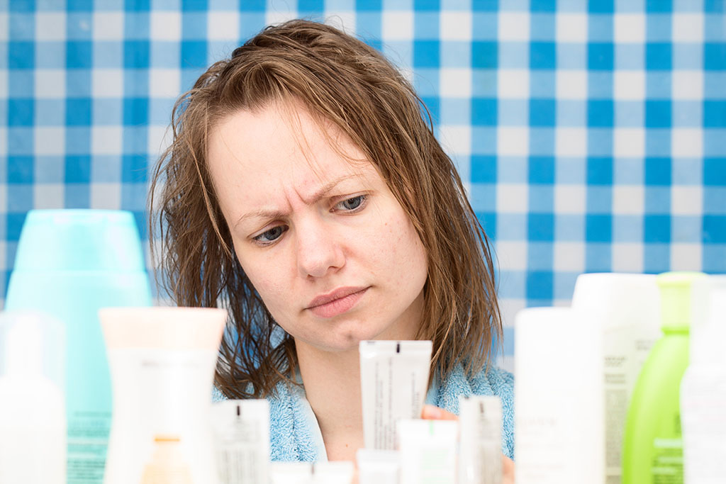 messy brunette woman with acne on skin reading makeup ingredients labels to see if safe
