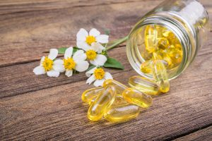 vitamin e in pill form in jar next to flower on wood