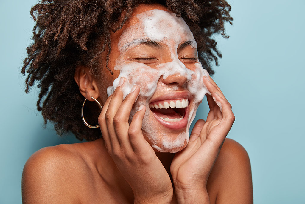 woman wearing hoop earrings laughs smiles while using bubbling facial cleanser on clear skin