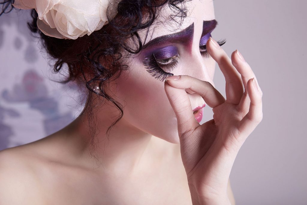women in dramatic halloween makeup and flower in hair removing her fake eyelashes