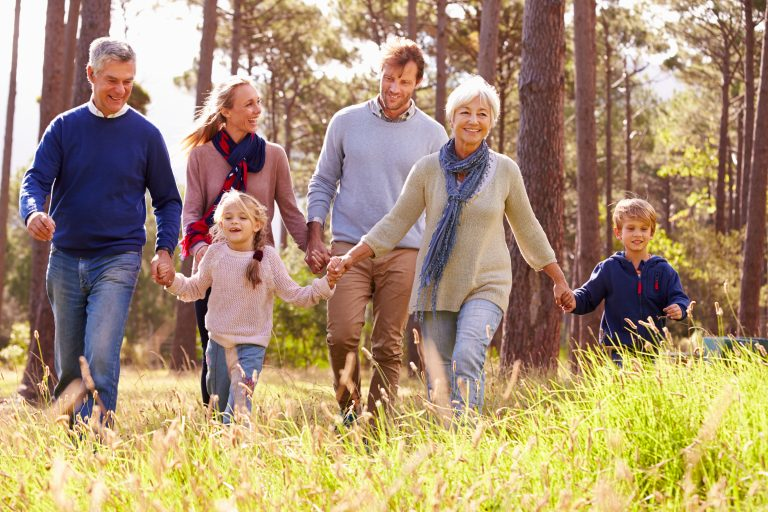 family of grandparents parents and kids walking through forest field holding hands for evening walk