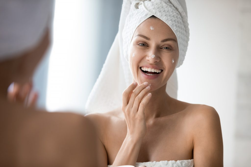woman apply cream on her face for night routine in towel and robe