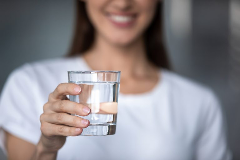 young woman smiling and holding glass of water to drink